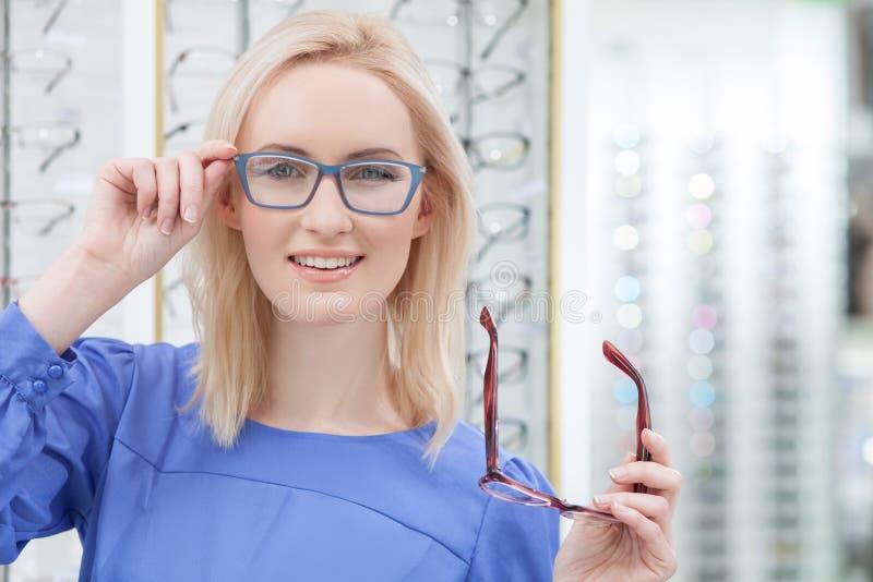 La giovane donna attraente sta indossando gli occhiali in negozio immagine stock