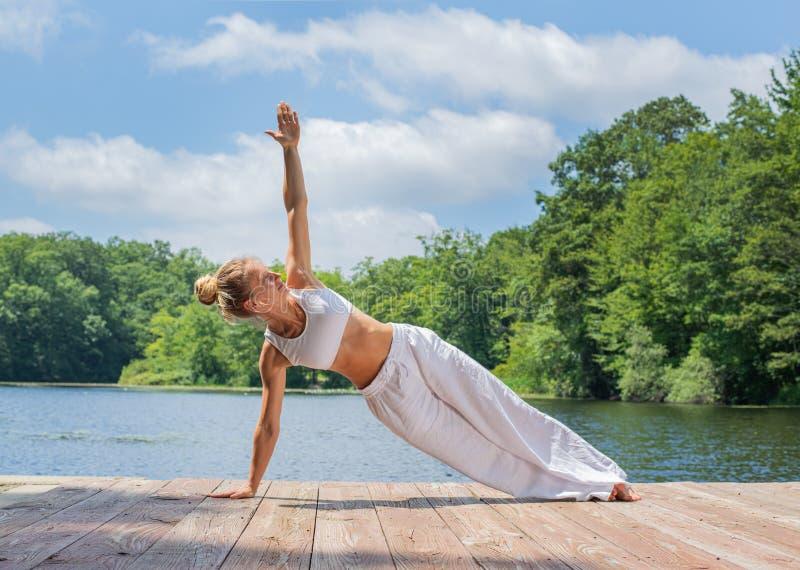 La giovane donna attraente sta praticando l'yoga, facente la posa di Camatkarasana vicino al lago fotografia stock libera da diritti