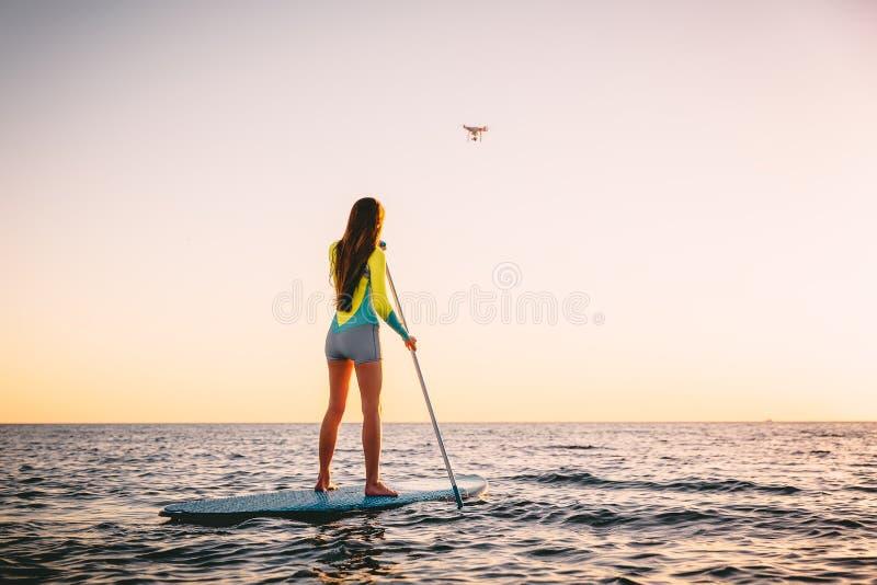 La giovane donna attraente sta su praticare il surfing della pagaia e l'elicottero del fuco con i bei colori del tramonto immagine stock libera da diritti