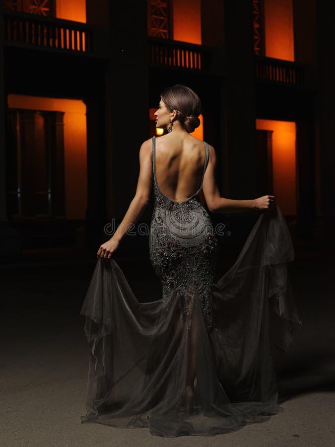 La giovane donna ben vestito seducente ed attraente con l'acconciatura in una sera astuta d'altezza ha decorato il vestito costos fotografia stock libera da diritti