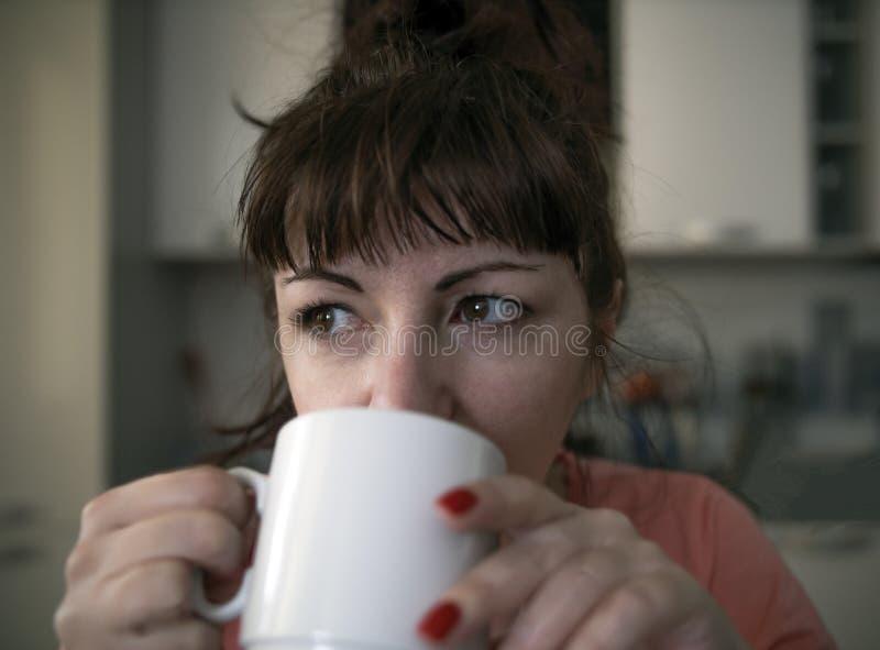 La giovane donna beve il caffè di mattina nella cucina, occhi stanchi con le vene rosse, primo piano fotografia stock