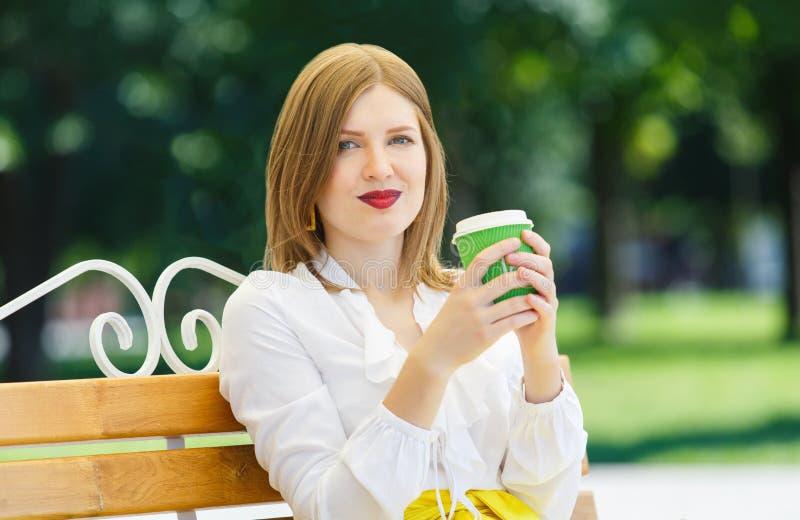 La giovane donna beve il caffè nel parco fotografia stock
