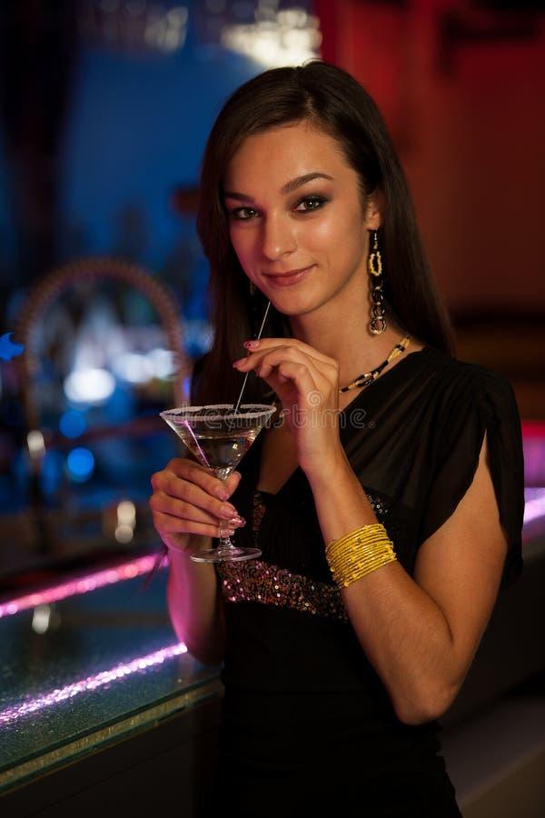 La giovane donna beve un cocktail in night-club fotografie stock libere da diritti