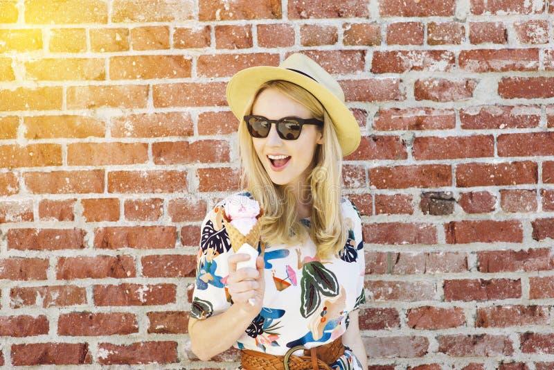 La giovane donna bianca tiene un cono gelato con le tonalità e Fedora di estate immagine stock