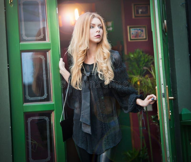 La giovane donna bionda affascinante in attrezzatura nera che posa in un verde ha dipinto la struttura di porta Giovane donna spl immagini stock
