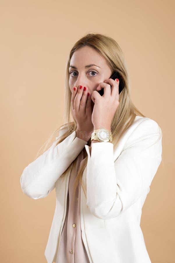 La giovane donna bionda attraente che parla sul telefono ed è sorpresa fotografia stock