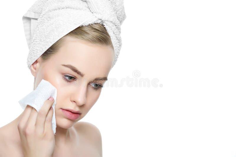 La giovane donna bionda attraente con i suoi capelli avvolti in un asciugamano, rimuovente compone facendo uso della strofinata m fotografie stock