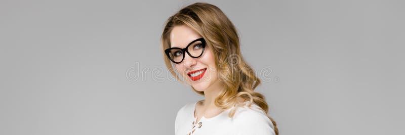 La giovane donna bionda attraente di affari in bianco e nero copre la lavagna per appunti sorridente della tenuta che sta di uffi fotografia stock