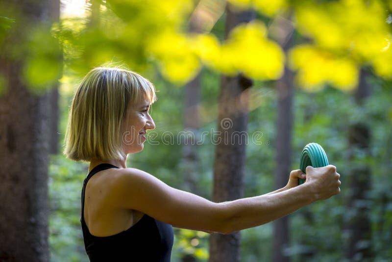 La giovane donna bionda che fa i pilates alimenta l'esercizio che piega una gomma immagini stock