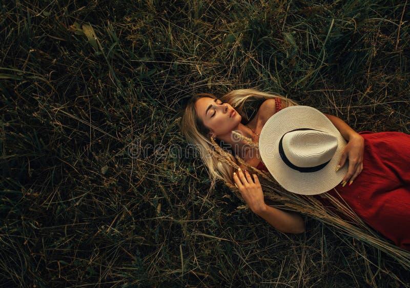 La giovane donna bionda con il cappello sta trovandosi sul prato fra le orecchie dell'erba fotografia stock libera da diritti