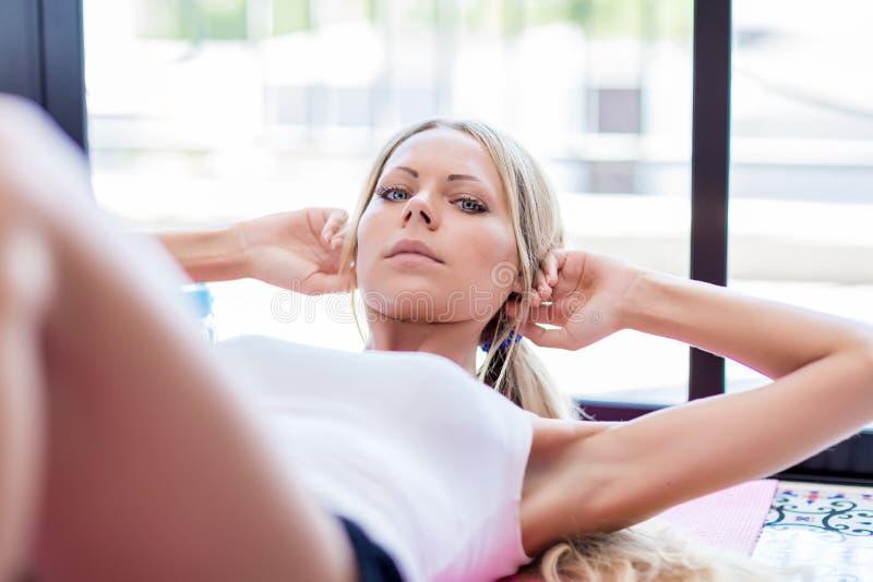 La giovane donna bionda fa l'esercizio addominale di sedere-UPS sulla stuoia ad uff fotografia stock