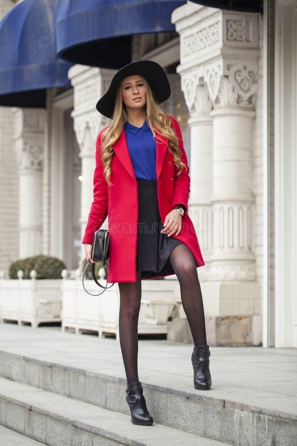 La giovane donna bionda felice in cappotto rosso cammina sulla via della molla fotografia stock libera da diritti
