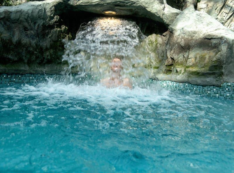 La giovane donna bionda sexy gode dell'acqua di caduta dietro la cascata nello stagno della stazione termale fotografie stock