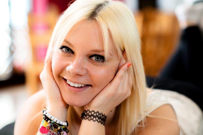 La giovane donna bionda sta sorridendo immagine stock libera da diritti