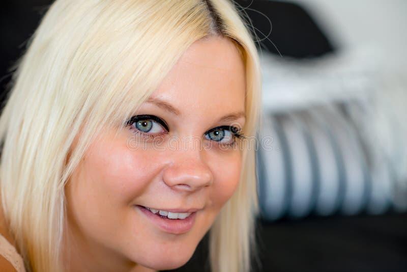 La giovane donna bionda sta sorridendo fotografia stock