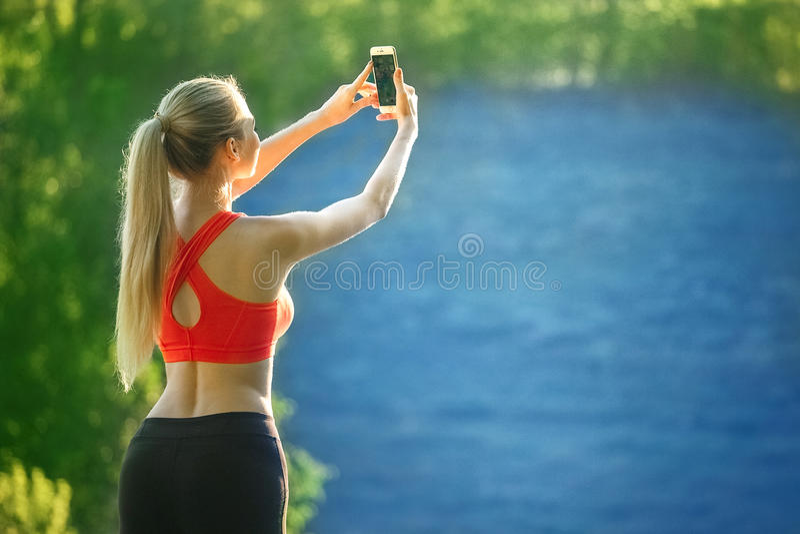 La giovane donna bionda sta su un fondo blu del mare La donna di sport in maglietta rossa fa il selfie sulla natura vicino al mar fotografie stock libere da diritti