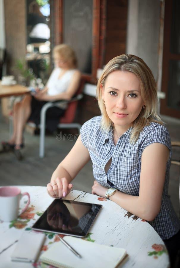La giovane donna in caffè utilizza una compressa per lavoro immagine stock libera da diritti