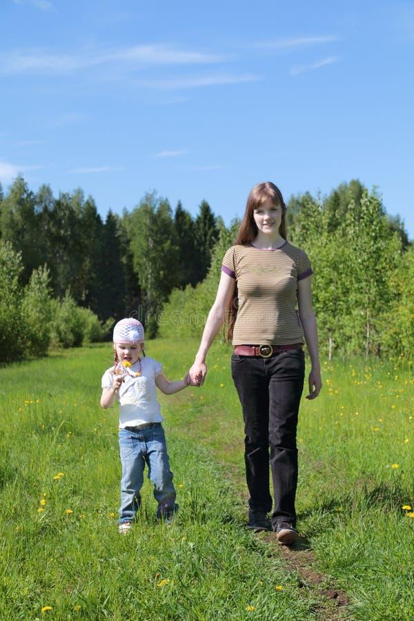 La giovane donna cammina con la figlia vicino alla foresta verde immagine stock