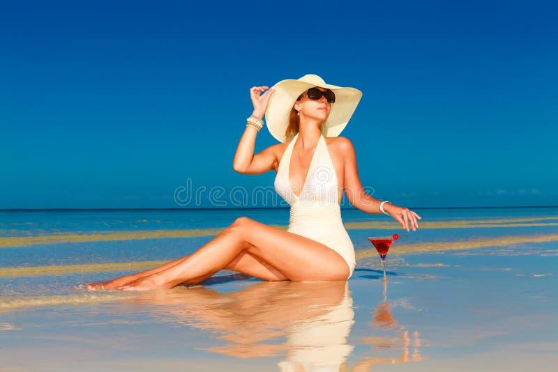 La giovane donna in cappello di paglia che si siede alla spiaggia tropicale e gode di immagini stock