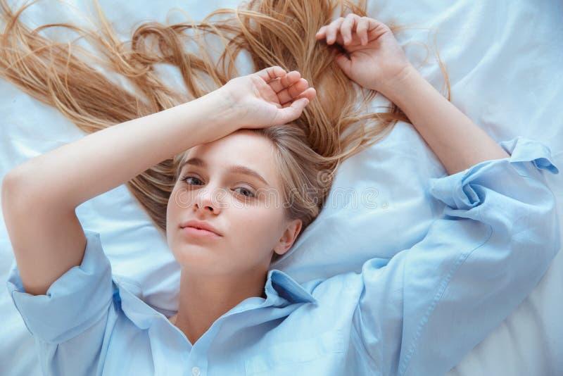 La giovane donna a casa che si situa a letto ha svegliato la sensualità di vista superiore fotografia stock libera da diritti