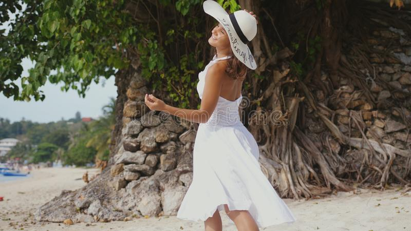 La giovane donna castana con capelli lunghi in drees e nelle passeggiate bianchi del cappello gode di sulla spiaggia tropicale immagini stock libere da diritti
