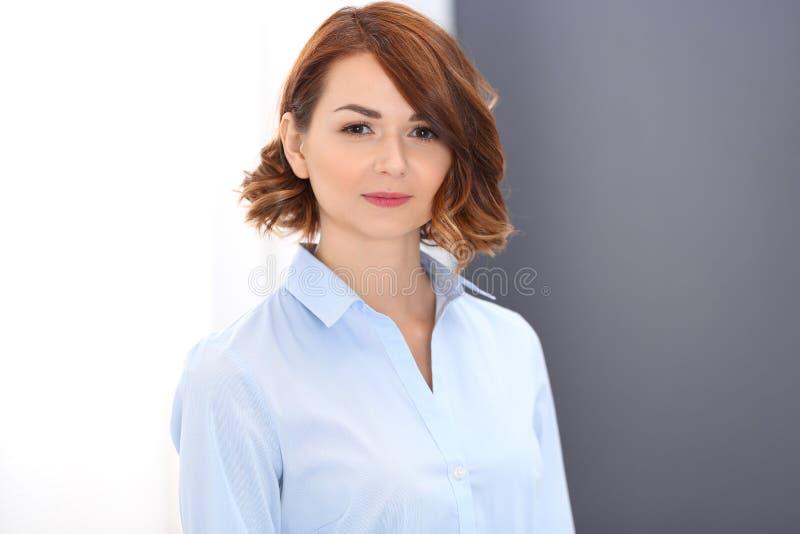 La giovane donna castana di affari assomiglia ad una ragazza dello studente che lavora nell'ufficio Ragazza caucasica che sta dir fotografie stock libere da diritti