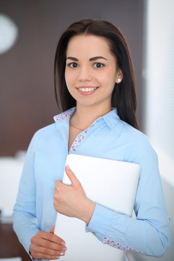 La giovane donna castana di affari assomiglia ad una ragazza dello studente che lavora nell'ufficio Condizione ispana o dell'Amer immagini stock libere da diritti