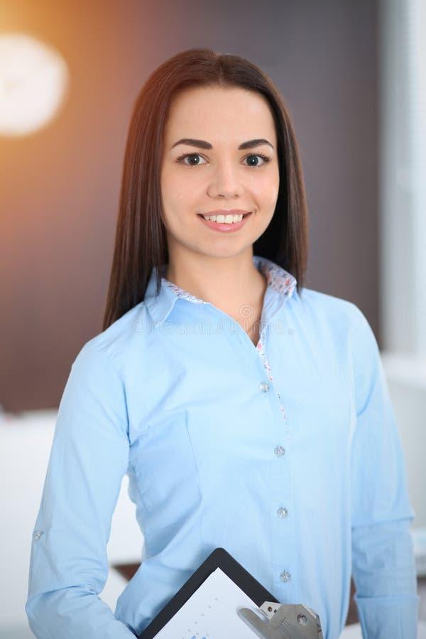 La giovane donna castana di affari assomiglia ad una ragazza dello studente che lavora nell'ufficio Condizione ispana o dell'Amer fotografia stock