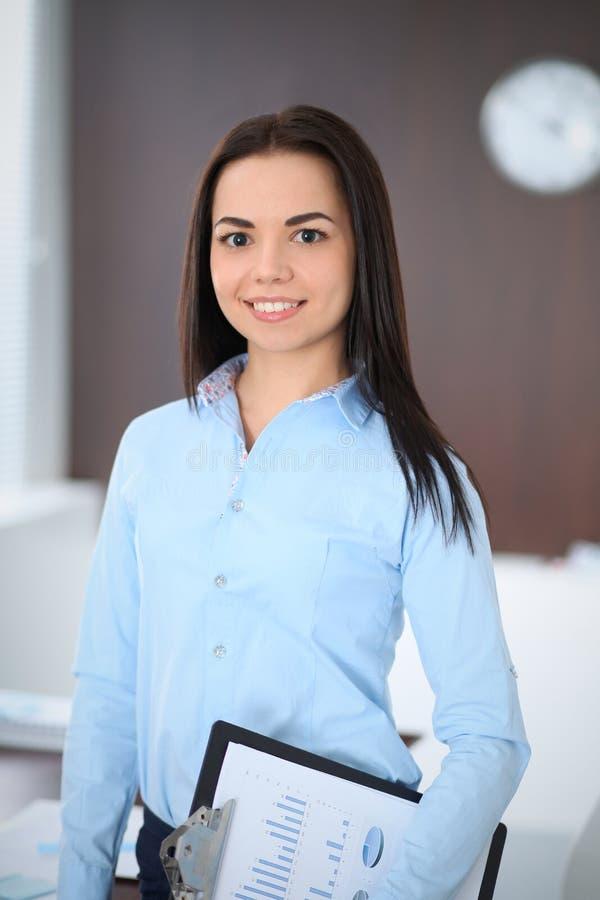 La giovane donna castana di affari assomiglia ad una ragazza dello studente che lavora nell'ufficio Condizione ispana o dell'Amer immagine stock libera da diritti