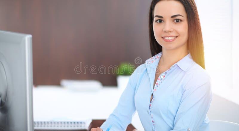 La giovane donna castana di affari assomiglia ad una ragazza dello studente che lavora nell'ufficio Ragazza ispana o dell'America immagini stock