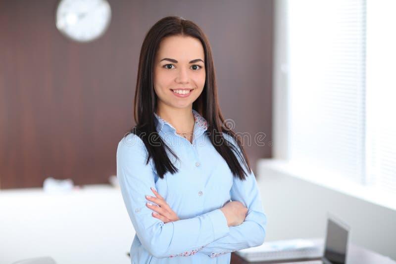 La giovane donna castana di affari assomiglia ad una ragazza dello studente che lavora nell'ufficio Ragazza ispana o dell'America immagine stock libera da diritti