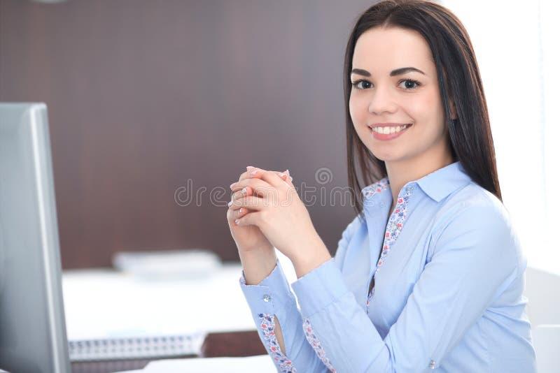 La giovane donna castana di affari assomiglia ad una ragazza dello studente che lavora nell'ufficio Ragazza ispana o dell'America immagine stock