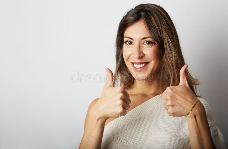 La giovane donna castana estatica felice con capelli lunghi completamente acconsente sopra fondo bianco vuoto Ragazza che mostra  immagini stock