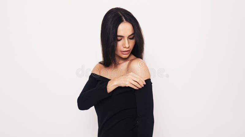 La giovane donna castana raddrizza il vestito immagine stock