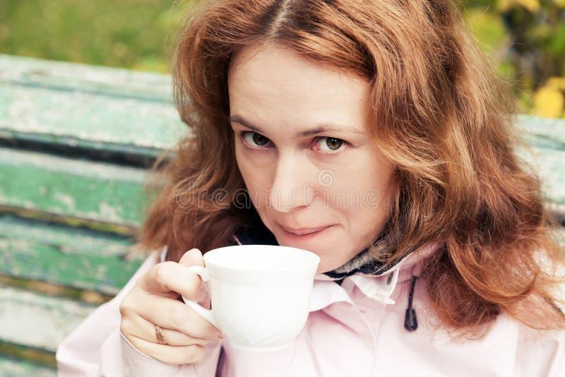 La giovane donna caucasica adulta beve il caffè in parco fotografia stock