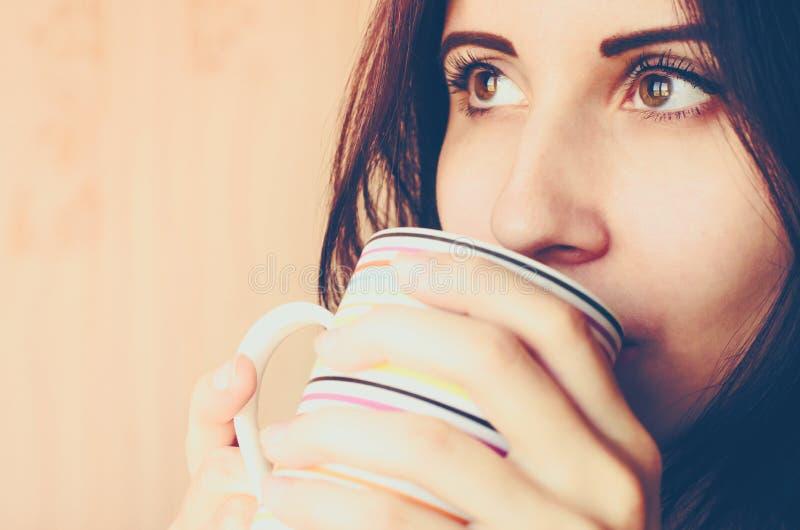La giovane donna caucasica beve una tazza della fine del tè sullo spazio della copia del ritratto immagini stock libere da diritti