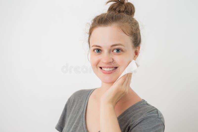 La giovane donna caucasica pulire il fronte con una strofinata, rimuovente compone fotografia stock