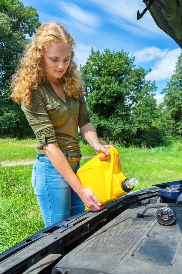 La giovane donna caucasica riempie il motore dell'automobile di olio fotografie stock libere da diritti