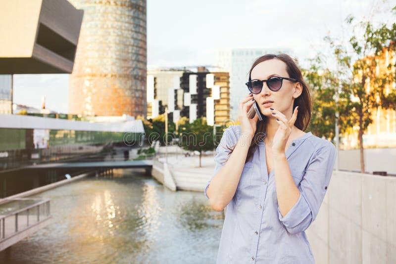 La giovane donna caucasica sorridente di affari sta parlando sullo Smart Phone vicino ai grattacieli fotografie stock