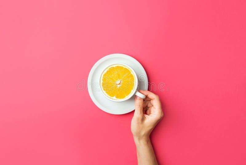 La giovane donna caucasica tiene con la tazza di caffè macchiato della mano con l'arancia divisa in due fresca nel mezzo su fondo fotografia stock