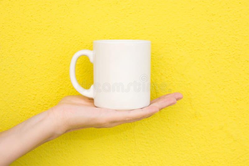 La giovane donna caucasica tiene a disposizione la tazza bianca del modello in bianco della palma sulla parete dipinta giallo lum fotografia stock