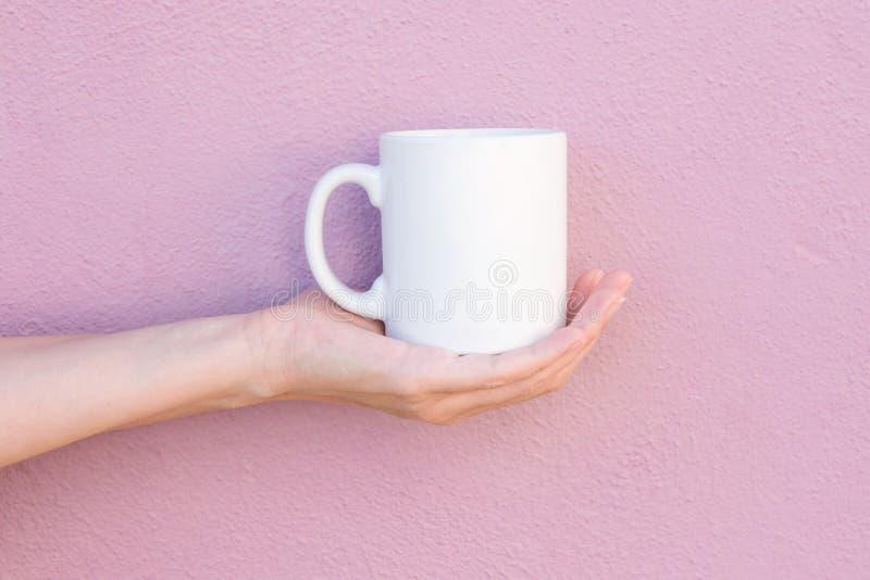 La giovane donna caucasica tiene a disposizione la tazza bianca del modello in bianco della palma sulla parete dipinta rosa-chiar fotografia stock libera da diritti