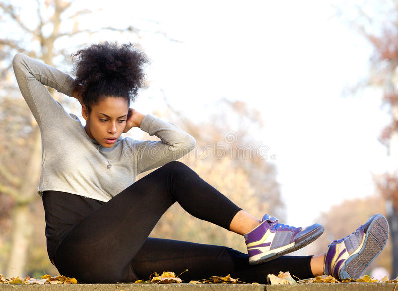 La giovane donna che afroamericana esercitarsi si siede aumenta fotografie stock