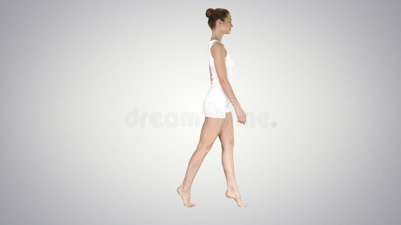 La giovane donna che cammina sulle sue punte dei piedi sul fondo di pendenza fotografie stock libere da diritti