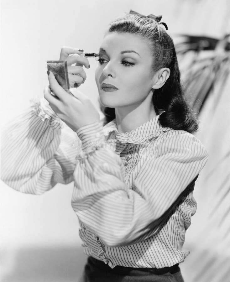 La giovane donna che esamina uno specchio e che mette sopra compone (tutte le persone rappresentate non sono vivente più lungo e  immagine stock libera da diritti