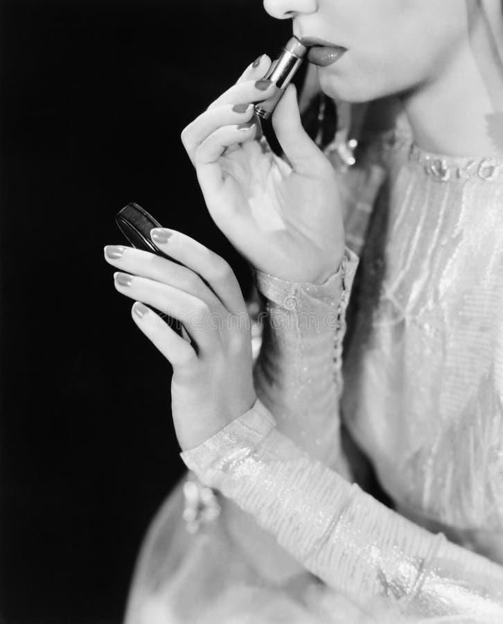 La giovane donna che esamina uno specchio e che mette sopra compone (tutte le persone rappresentate non sono vivente più lungo e  fotografia stock libera da diritti