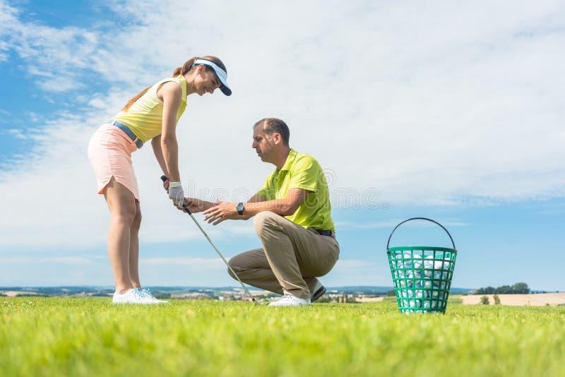 La giovane donna che esercita l'oscillazione del golf ha aiutato dal suo istruttore fotografia stock libera da diritti
