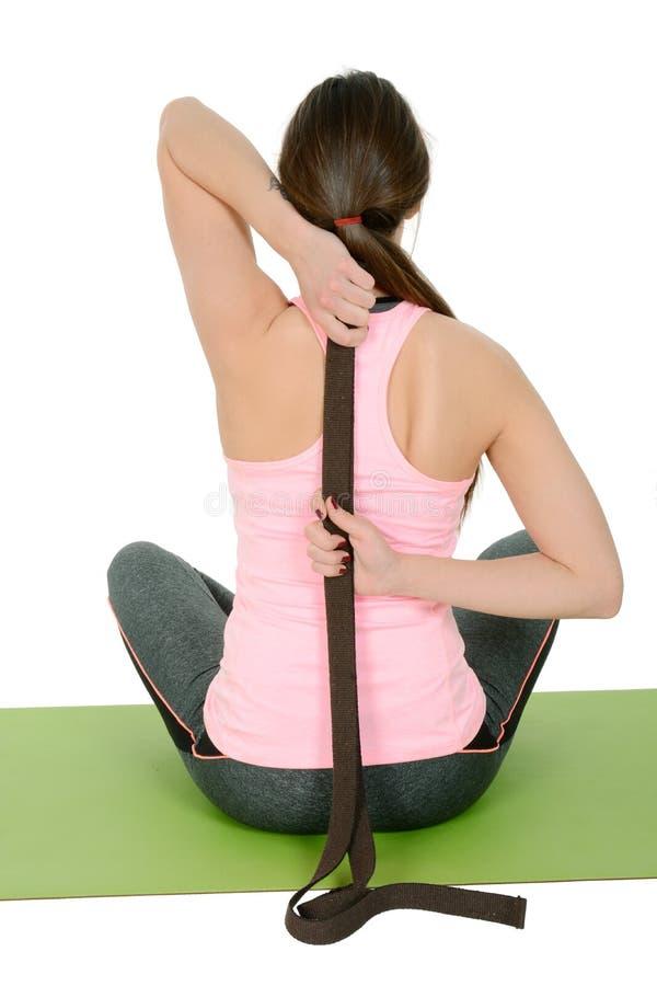 La giovane donna che fa l'yoga facendo uso della cinghia gradisce i puntelli immagine stock