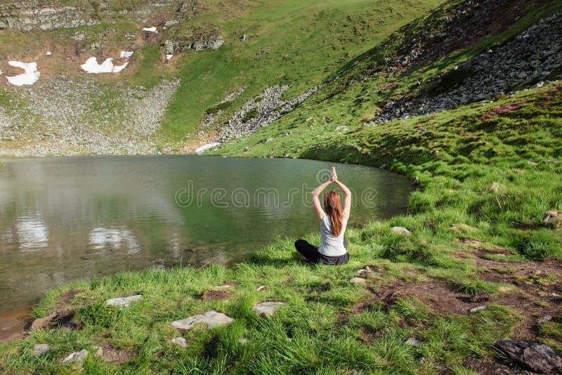 La giovane donna che fa l'yoga si esercita vicino al lago fotografie stock