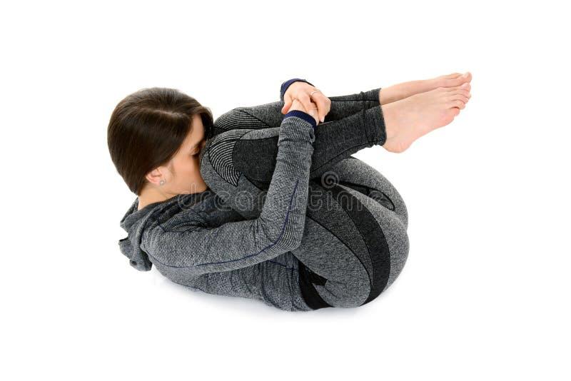 La giovane donna che fa l'yoga supina semplice di asana di yoga posa immagini stock